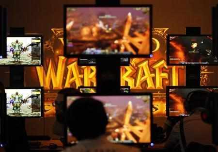 Visitors play ''World of Warcraft'' at an exhibition stand during the Gamescom 2011 fair in Cologne August 17, 2011.    REUTERS/Ina Fassbender