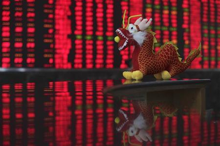 A toy dragon decoration for the upcoming Chinese Lunar New Year is seen in front of an electrical board showing stock information at a brokerage house in Wuhan, Hubei province January 19, 2012. REUTERS/Stringer