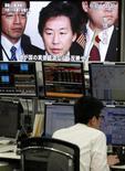 Валютный дилер за рабочим столом на фоне телеэкрана, показывающего кадры выступления министра финансов Японии Дзюна Адзуми в Токио, 31 октября 2011 года. Министр финансов Японии Дзюн Адзуми сказал в пятницу, что решил провести интервенцию на валютном рынке в прошлом году, чтобы опустить иену с уровня 75,63 иены за доллар. REUTERS/Yuriko Nakao