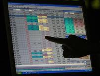 Фондовый брокер показывает пальцем на котировки на экране компьютера в помещении фондовой биржи в Карачи 6 августа 2008 года. Фонды, ориентированные на акции РФ, продолжают привлекать неплохие объемы новых средств, поддерживаемые возросшим аппетитом глобальных инвесторов к риску, свидетельствует исследование EPFR Global, на которое ссылаются Уралсиб, ВТБ Капитал и Альфа-банк. REUTERS/Athar Hussain