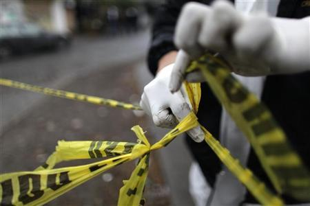 A forensic technician ties a used police line together to seal off a crime scene in Monterrey February 8, 2012. REUTERS/Daniel Becerril