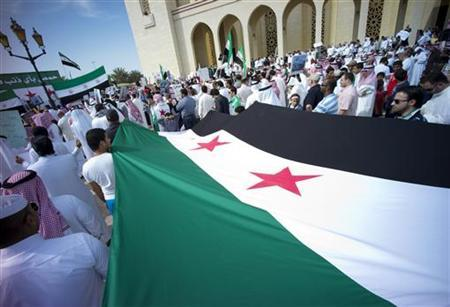 Syrian revolution flags are held up by protesters during an anti-Syrian President Bashar al-Assad protest held at Fateh Mosque after the Friday prayers in Manama, February 10, 2012. REUTERS/Hamad I Mohammed