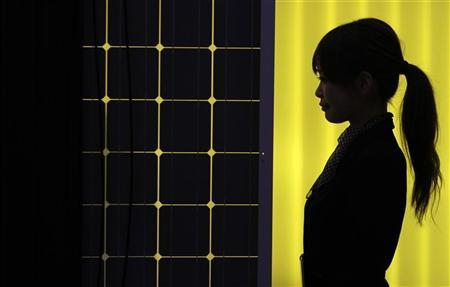 A woman is silhouetted next to a solar panel display by solar module supplier Upsolar at the fourth International Photovoltaic Power Generation (PV) Expo in Tokyo March 2, 2011.  REUTERS/Yuriko Nakao