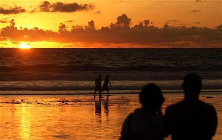 Tourists watch the sunset from Kuta beach in Indonesia's resort island of Bali February 2, 2010.  REUTERS/Murdani Usman