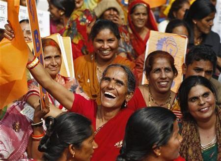 Activists from the Indian Workers Union smile during a protest against the ruling government in New Delhi November 23, 2011. REUTERS/Parivartan Sharma/Files