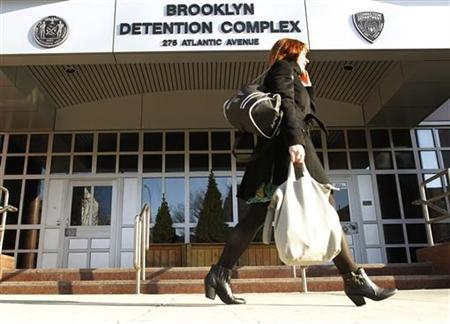 A woman walks with groceries past the public entrance to the Brooklyn Detention Center in the Brooklyn borough of New York, February 10, 2012. The jail, which fills a city block and has been shuttered for the past decade, reopened this week in a newly upscale neighborhood following a legal fight over its proposed expansion. REUTERS/Brendan McDermid