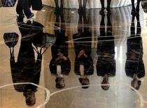 A porter carries luggage past a group of reception staff that are reflected in the floor as they stand in the foyer of the five-star rated Sofitel Hotel in Beijing November 19, 2007. REUTERS/David Gray