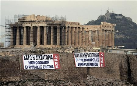 Two anti-austerity banners, placed by activists of the Greek Communist party, are displayed on a hill at the Acropolis in Athens February 11, 2012. REUTERS/Eurokinissi/Antonis Nikolopoulos