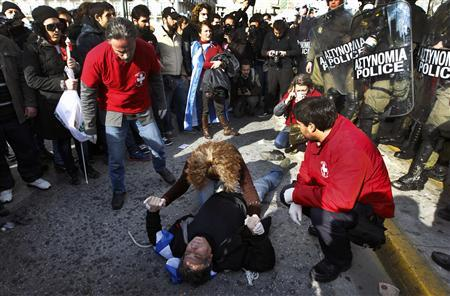Medics try to help an anti-austerity protester, who lies unconscious after he was injured by police, in front of the parliament in Athens February 11, 2012, during a demonstration on the second day of a 48-hour strike by Greek workers unions. REUTERS/Yannis Behrakis
