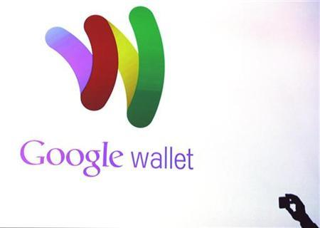 An attendee takes a photo of the Google wallet application screen during a news conference unveiling the mobile payment system in New York May 26, 2011. REUTERS/Shannon Stapleton/Files