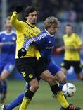 Kiessling, do Bayer Leverkusen, disputa a bola com Hummels, do Borussia Dortmund, durante jogo da primeira divisão da Bundesliga, em Dortmund. O atual campeão Borussia Dortmund manteve sua vantagem de dois pontos na liderança do campeonato alemão neste sábado após a vitória por 1 x 0 sobre o Bayer Leverkusen 11/02/2012.  REUTERS/Ina Fassbender