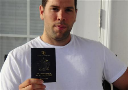 Former U.S. citizen Adam Bilzerian holds up his St. Kitts and Nevis passport, outside his home in Basseterre January 31, 2012. Bilzerian, son of former corporate raider Paul Bilzerian, renounced his U.S. citizenship in 2008 after becoming disenchanted with its politics and acquiring a St. Kitts and Nevis passport through a ''citizenship by investment'' program. This two-island nation is one of three countries offering so-called citizenship by investment, burgeoning programs that bestow on foreigners the benefits of being a citizen - namely, a passport for a price. Picture taken January 31.   REUTERS/Stanford Conway