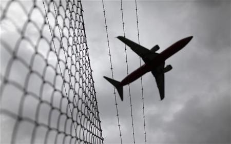 A passenger plane flies over a barbed wire fence as it approaches an airport in this February 23, 2010 file photo. REUTERS/Tim Wimborne