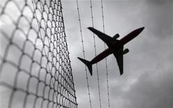 <p>A passenger plane flies over a barbed wire fence as it approaches an airport in this February 23, 2010 file photo. REUTERS/Tim Wimborne</p>