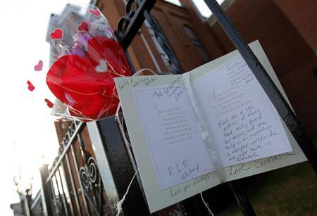 Flowers and a card are seen left as a memorial to deceased singer Whitney Houston, in front of the New Hope Baptist Church, where she sang in the choir, in Newark, New Jersey, February 12, 2012. REUTERS/Adam Hunger