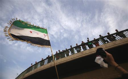 A demonstrator waves a Syrian flag during a protest against Syria's President Bashar al-Assad, upon the meeting of the Arab Foreign ministers in Cairo February 12, 2012.      REUTER/Mohammed Salem