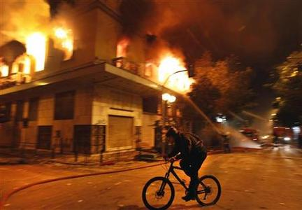 A cyclist rides past a burning building during violent protests in central Athens, February 12, 2012. REUTERS/Yannis Behrakis