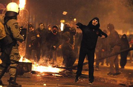 A protester hurls rocks at police during a violent anti-austerity demonstration in central Athens February 12, 2012. REUTERS-Yannis Behrakis