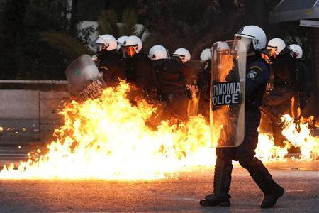 A petrol bomb explodes near riot police during a huge anti-austerity demonstration in Athens' Syntagma (Constitution) square February 12, 2012. REUTERS-Yiorgos Karahalis