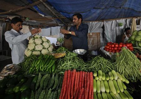 A customer pays after buying vegetables from a street side vendor in Mumbai January 31, 2012. REUTERS/Danish Siddiqui