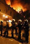 Члены отряда полиции стоят со щитами во время акции протеста в Афинах, 12 февряля 2012 года. Греческий парламент одобрил крайне непопулярные меры бюджетной экономии в ночь с воскресенья на понедельник ради получения второй программы финансовой помощи от Европейского союза и Международного валютного фонда, которая должна помочь стране избежать неконтролируемого дефолта по своим долгам. REUTERS/Yannis Behrakis