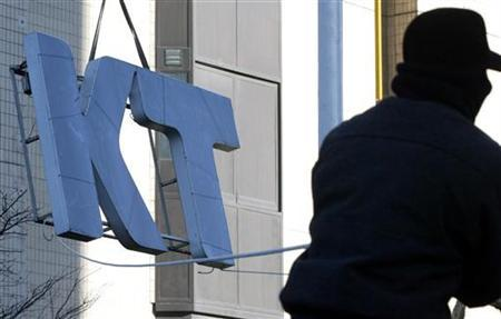 A South Korean worker pulls down a signboard of KT Corp. in Seoul December 26, 2005. REUTERS/Lee Jae-Won/Files