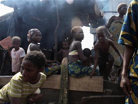 Residents of the Makoko fishing community in Lagos stand outside their house, November 21, 2009.  REUTERS/Goran Tomasevic