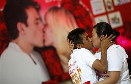 Couple kiss among others participating in the Guinness World Record attempt in the longest continuous kiss in Pattaya February 12, 2012.  REUTERS/Damir Sagolj