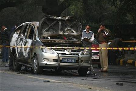Police and forensic officials examine a damaged Israeli embassy car after an explosion in New Delhi February 13, 2012. REUTERS/Parivartan Sharma
