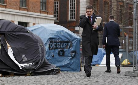 A man talks on the phone as he walks past tents in the Occupy London encampment outside St. Paul's Cathedral in London, February 13, 2012. REUTERS/Suzanne Plunkett