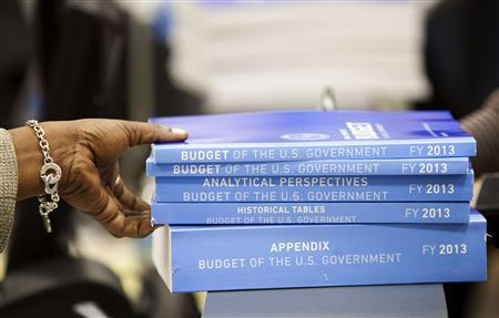 A cashier holds copies of the 2013 Federal Budget at the Government Printing Office in Washington February 13, 2012.      REUTERS/Joshua Roberts