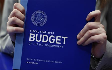 A staff assistant holds a copy of President Obama's FY2013 budget upon its arrival at the Senate Budget Committee room on Capitol Hill in Washington February 13, 2012.       REUTERS/Kevin Lamarque