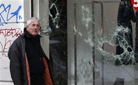 A man passes smashed store windows after a night of violence which followed the Greek parliament approval of a deeply unpopular austerity bill in Athens, February 13, 2012. Police said 150 shops were looted in the capital and 48 buildings set ablaze.  REUTERS/John Kolesidis