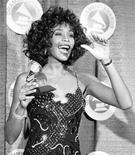 Whitney Houston posa com seu Grammy após ter sido nominada Melhor Vocalista Pop - Feminino nos 30th Grammy Awards, 2 de março de 1988. A estrela pop foi encontrada debaixo d'água e aparentemente inconsciente na banheira de um hotel de Beverly Hills, informou a polícia nesta segunda-feira. REUTERS/Mark Peterson