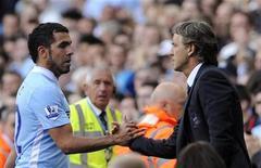 O técnico do Manchester City Roberto Mancini (direita) substitui Carlos Tevez durante seu jogo da English Premier League contra o Wigan Athletic em Manchester, 10 de setembro de 2011. O atacante disse que se o técnico Roberto Mancini estiver sendo sincero sobre tê-lo de volta no time ele ficaria feliz em voltar. REUTERS/Nigel Roddis