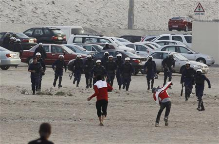 An anti-government protesters throw rocks at riot police after protesters broke through police barriers to run towards Farooq Junction formerly known as Pearl Square during a protest in Budaiya west of Manama, February 13, 2012. REUTERS/Hamad I Mohammed