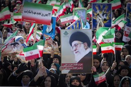 Demonstrators wave the Iranian flag and hold a picture of Supreme Leader Ayatollah Ali Khamenei during a ceremony to mark the 33rd anniversary of the Islamic Revolution, in Tehran's Azadi square, February 11, 2012. REUTERS/Caren Firouz