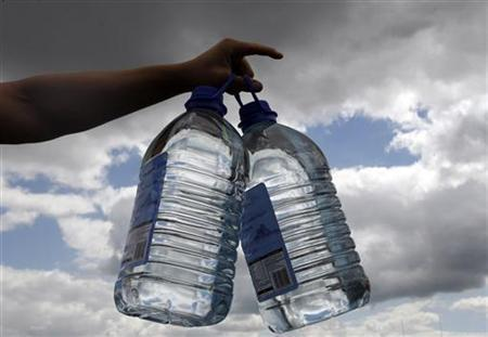 A volunteer gives out bottles of drinking water, central England, July 24, 2007. REUTERS/Darren Staples