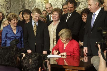 Washington state Governor Christine Gregoire signs legislation legalizing gay marriage in the state, in Olympia, Washington February 13, 2012. REUTERS/Robert Sorbo