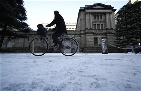A man cycles in front of the Bank of Japan (BOJ) headquarters covered with snow in Tokyo January 24, 2012. REUTERS/Toru Hanai