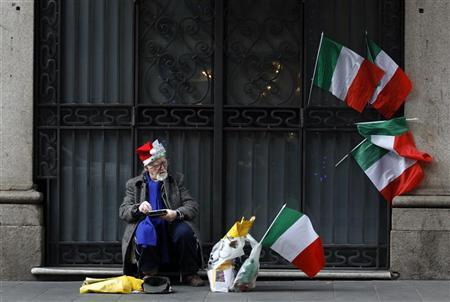 A street beggar wears a Santa Claus hat in downtown Rome December 16, 2011. REUTERS/Alessandro Bianchi