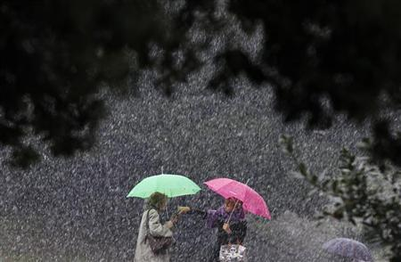 Women chat with each other as they protect themselves from the falling snow with umbrellas in front of Rome's ancient Colosseum February 3, 2012.  REUTERS/Alessandro Bianchi
