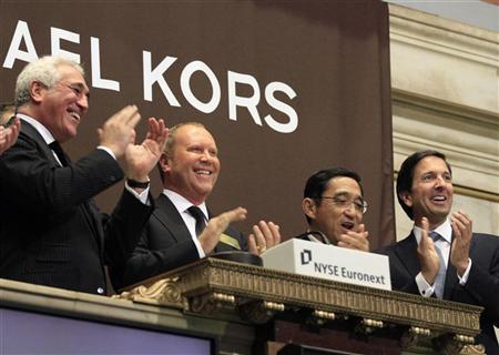 Designer Michael Kors (2nd L) celebrates after ringing the opening bell with guests of Michael Kors Holdings Ltd. at the New York Stock Exchange December 15, 2011. REUTERS/Brendan McDermid