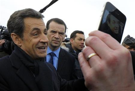 France's President Nicolas Sarkozy (L) is pictured as he shakes hands with people outside the French solar panel maker PhotoWatt in Bourgoin-Jallieu, February 14, 2012.  REUTERS/Philippe Wojazer
