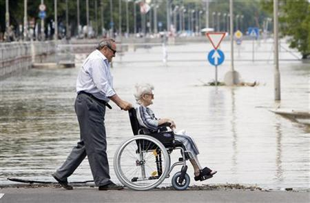 A man pushes his wheelchair-bound mother along the river bank of the flooded Danube river in Budapest June 7, 2010. REUTERS/Laszlo Balogh