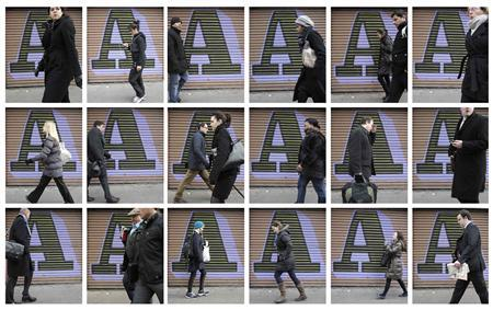 A combination photograph shows pedestrians passing a vacant shop door painted by graffitti artist Ben Eine, in the City of London financial district on February 14, 2012.  REUTERS/Chris Helgren