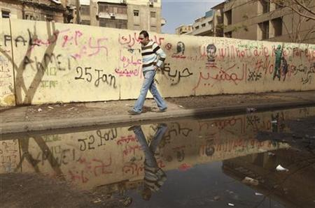 A man walks past a wall full of graffiti against the ruling military council near Tahrir square, February 8, 2012. REUTERS/Mohammed Salem