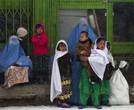 Mulher e crianças esperam por transportes enquanto neva em Cabul, 22 de janeiro de 2012. REUTERS/Ahmad Masood