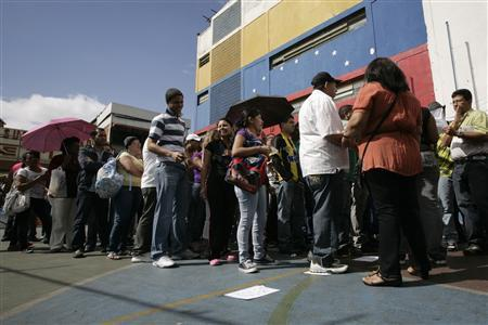 People line up to cast their votes at a polling station in Caracas February 12, 2012. Venezuelans voted on Sunday in an opposition primary expected to name a young state governor to challenge Hugo Chavez later this year at a close presidential election in South America's biggest oil exporter. REUTERS/Gil Montano
