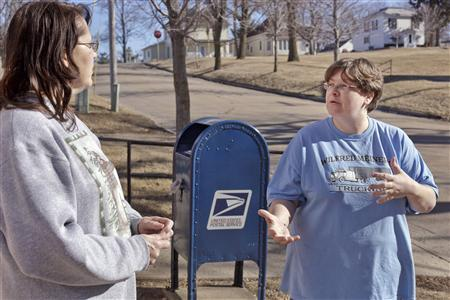 Cindy Riesselman (L) and Deborah Meiners discuss the effects that the closing of the local post office would have on their town, in Dedham, Iowa, January 31, 2012. Dedham is not alone in its dependence on the Postal Service. Some of America's poorest communities - most of them without broadband Internet coverage - stand to suffer most if the struggling agency moves ahead with plans to shutter thousands of post offices later this year, a Reuters analysis found. Many of the 4,200 post offices under consideration are in sparsely populated rural areas where poverty rates are higher than the national average, demographic data analyzed by Reuters shows.  REUTERS/Brian C. Frank